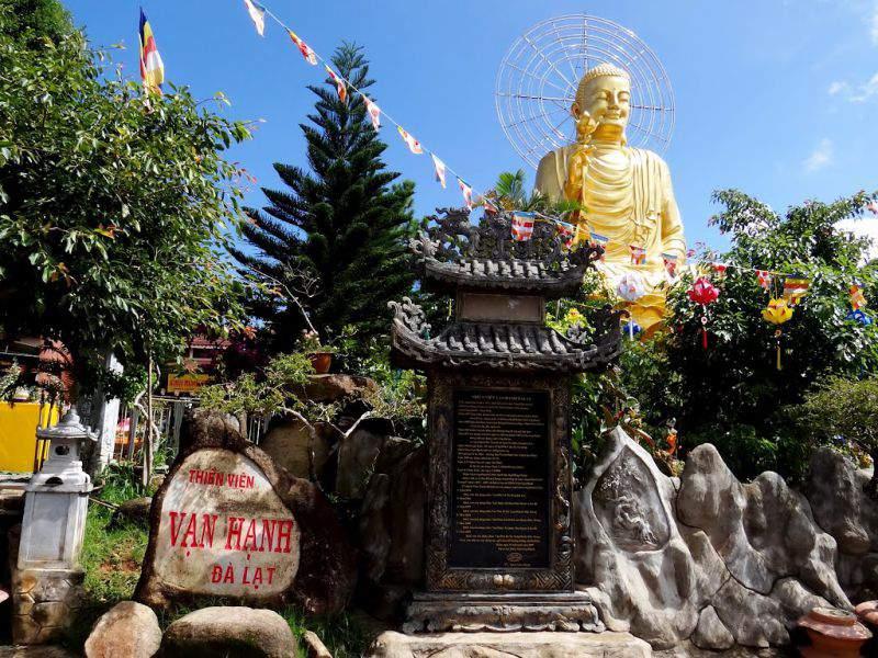 khuôn viên thiền viện Vạn Hạnh với bức tượng phật màu vàng lớn và những hàng cây xanh