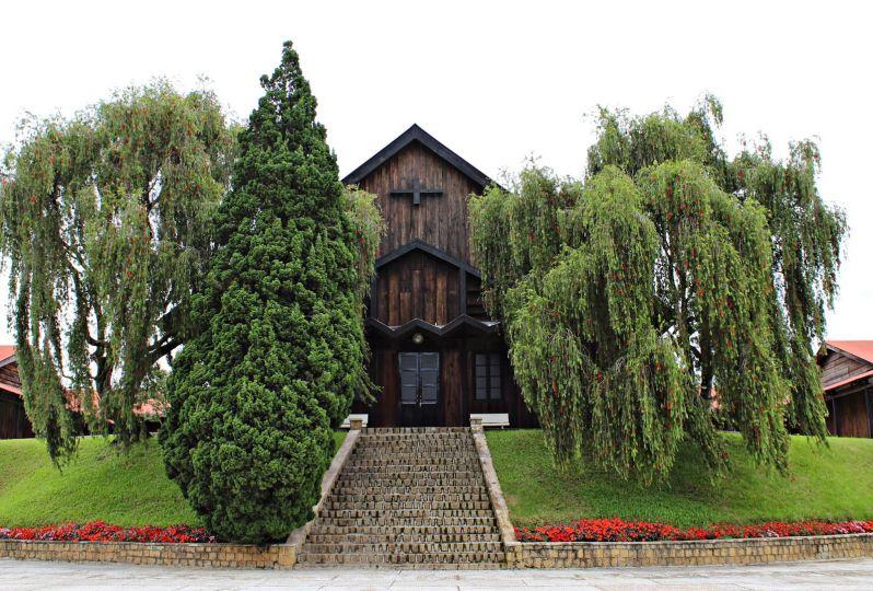 hình ảnh chủng viện Minh Hòa với ngôi nhà bằng gỗ và khuôn viên cây xanh