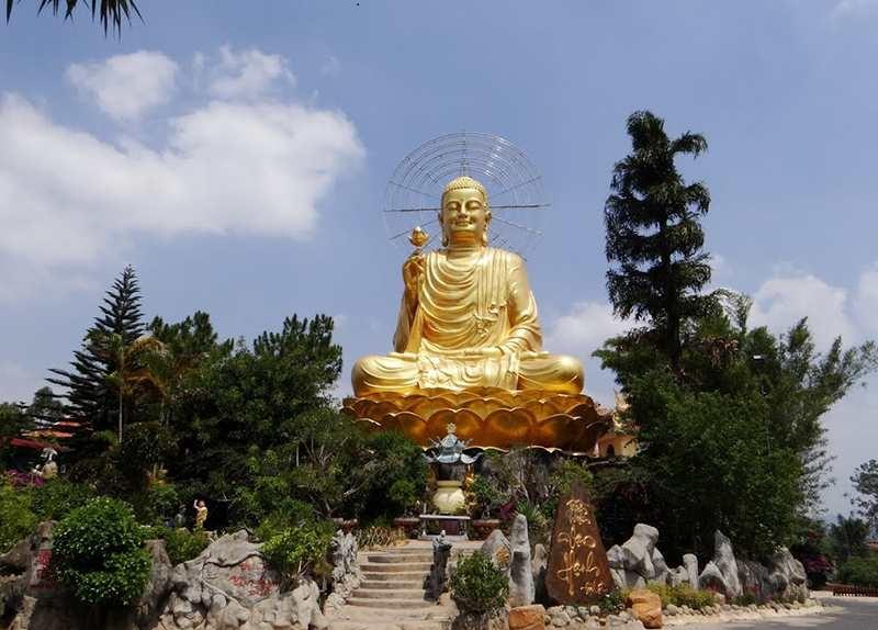 bức tượng phật Thích Ca với màu vàng nỗi trội trong khuôn viên cây xanh ở thiền viện Vạn Hạnh