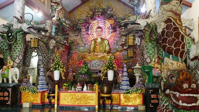 không gian bên trông chính điện với trang trí nhiều hình ảnh rồng và tượng đức phật uy nghi với tông màu vàng chủ đạo